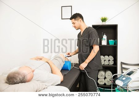 Physical Therapist Using Ultrasound Probe On Patient Knee While Standing In Hospital