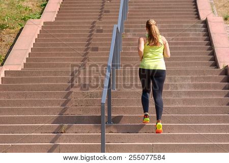 Full Length Rear View Of An Active And Determined Middle-aged Woman Running While Climbing Stairs Du