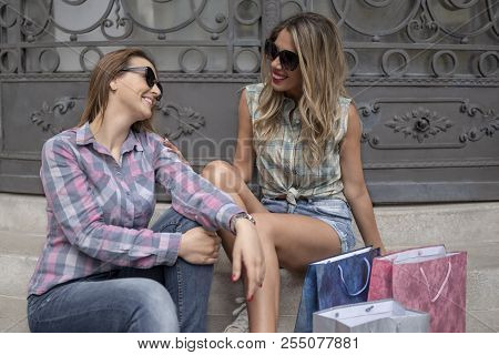 Two Attractive Smiling Girls With Shopping Bags Sitting On A Sunny Day After Shopping. Girls Talking