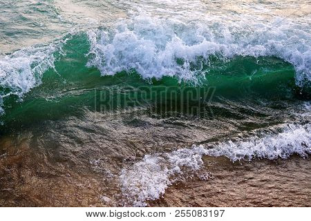 A Bright Green Wave Of Lake Michigan. Clear Water. White Foam On The Crest Of The Wave. The Wave Is