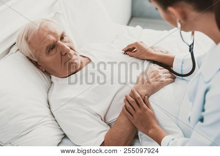 Young Female Doctor Examining Senior Patient. Closeup Of Young Woman Doctor Wearing White Coat Exami