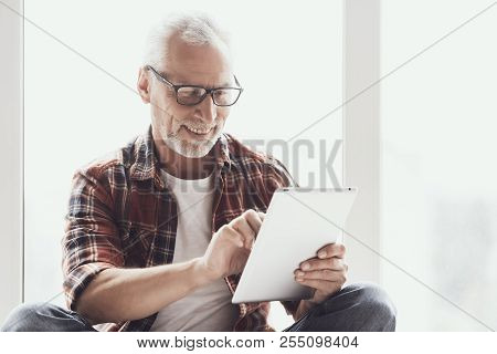 Smiling Mature Man With Beard Using Tablet At Home. Portrait Of Casual Adult Happy Man Wearing Glass