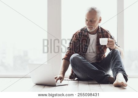Smiling Mature Man With Beard Using Laptop At Home. Casual Happy Adult Man Sitting On Floor And Drin