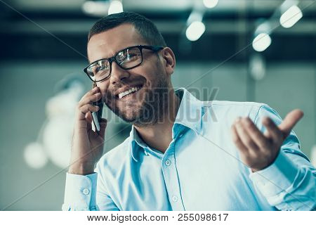 Young Smiling Businessman Talking On Phone. Happy Man Wearing Glases And Blue Shirt Talking On Smart