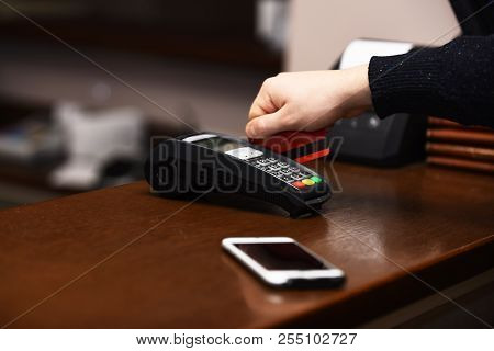 Male Hand Puts Bankcard Into Reader On Defocused Background. Credit Card Terminal For Cashless Payme