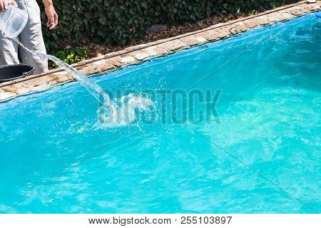 Man Pours Of Disinfectant In Outdoor Swimming Pool On Backyard Of Country House