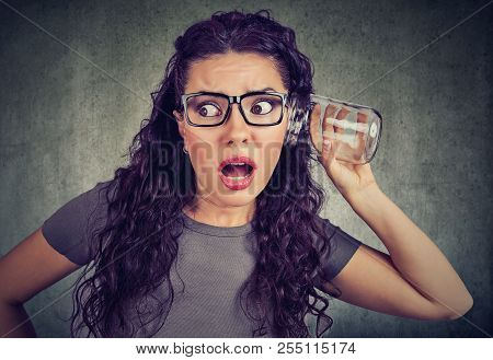 Young Funny Woman Eavesdropping With Glass Jar Looking Shocked While Listening To Secrets, Private C