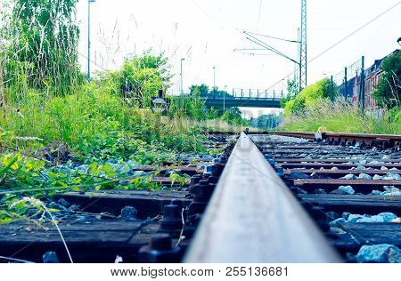 Railway Tracks In The Countryside With Track Bed. Gravel And Switch At A Railroad Crossing