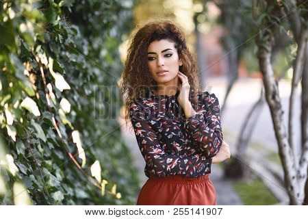 Beautiful Young Arabic Woman With Black Curly Hairstyle. Arab Girl Wearing Casual Clothes In The Str