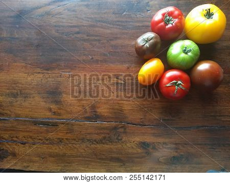 Delicious And Colorful Heirloon Tomatoes On A Wooden Table