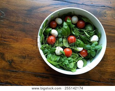 Tomatoes And Mozzarella - On A Salad Made From Very Tender Fresh Baby Spinach