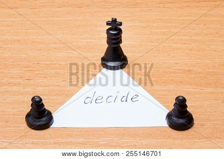Two Black Pawns And A Chess King Around A Paper Triangle With The Inscription To Decide