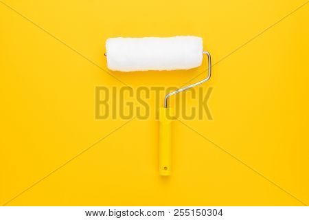 Clean Paint Roller. Paint Roller On The Yellow Background. Top View Of Paint Roller With Yellow Hand