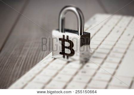 Padlock With Bitcoin Symbol And White Computer Keyboard On The Wooden Office Table. Blockchain Techn