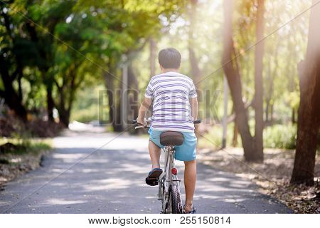 Asian Boy Ride Bicycle In A Park