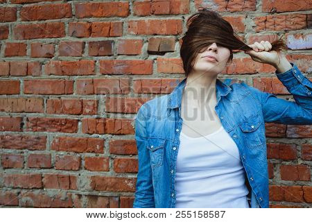 Adult Girl Hiding Her Eyes With Her Hair Standing In Denim Clothing And White T-shirt On Red Brick W