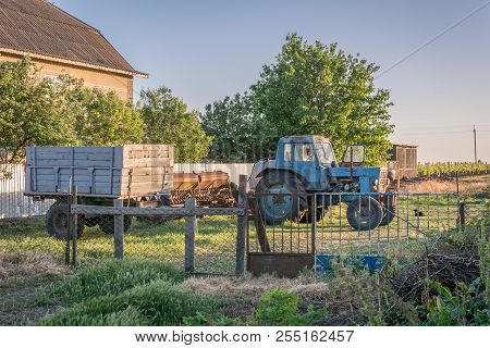 Old Blue Tractor, Trailer And Plow At Sunset