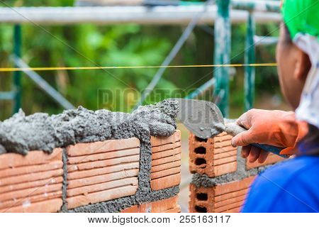 Construction worker using trowel to add cement mortar on top of the stacked terra cotta bricks to prepare for adding the next row, good for construction concept poster
