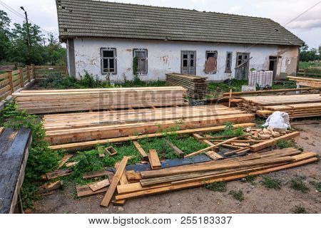 Wooden Beams For The Construction Of A Frame House On The Background Of An Old House