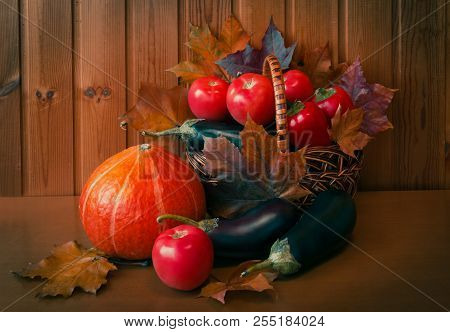 Fresh Vegetables In Basket And Near On Wooden Table Against Wall From Boards