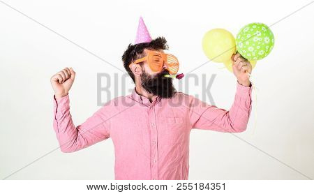 Guy In Party Hat With Air Balloons Celebrates. Man With Beard And Mustache On Busy Face Blows Into P