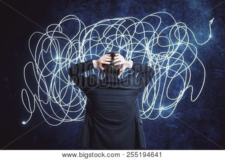 Back View Of Confused Young Businessman With Scribble Sketch. Confusion And Think Concept