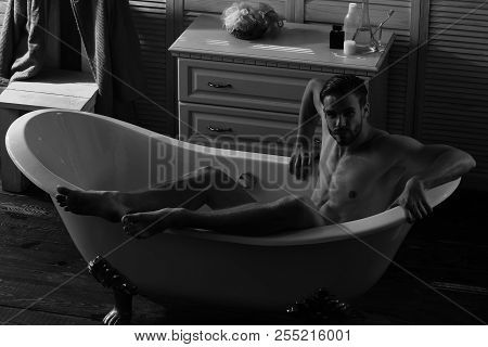 Man with beard and seductive face. Macho sitting naked in bathtub with erotic atmosphere around. Guy in bathroom with toiletries and chair on background. Sex and erotica concept. poster