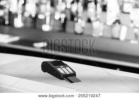 Red bankcard inserted in reader on defocused background. Payment for drink in bar. Credit card payment and electronic bank concept. EDC machine or credit card terminal for cashless payments. poster