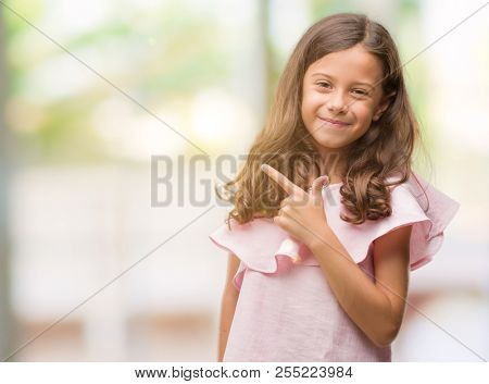 Brunette hispanic girl wearing pink dress cheerful with a smile of face pointing with hand and finger up to the side with happy and natural expression on face looking at the camera.