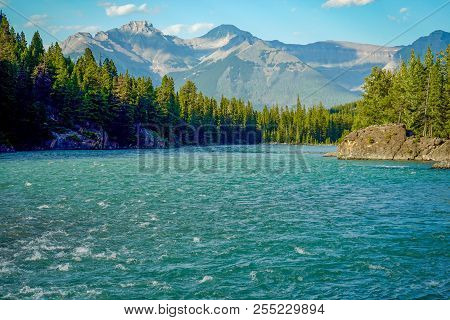 Blue Sky Over Bow River With Mountains And Trees In Banff, Alberta, Canada