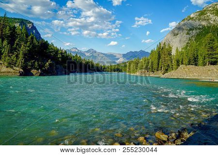 Beautiful Rocky Mountains And Flowing Water In Bow River In Banff, Alberta, Canada