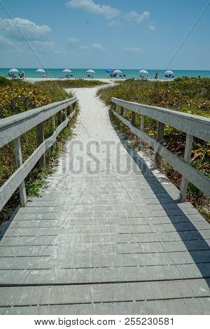 Dramatic Vertical View Of Wood Bridge Looking Toward A Sandy Ocean Beach With Colorful Umbrellas On
