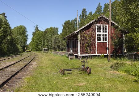 Old, Red, Wooden Building Beside The Railroad. Trolley This Side, Spring. Forest.