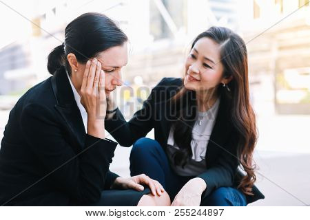 Businesswomen sit on the steps in the city, one of whom is comforting friend their project did not achieve the planned goal. poster
