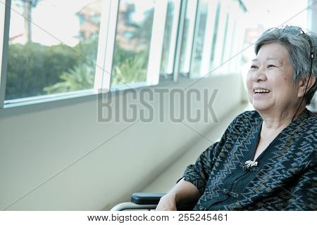 Asian Elder Woman On Wheelchair Smiling & Resting Near Window. Happy Elderly Female Relaxing Indoors