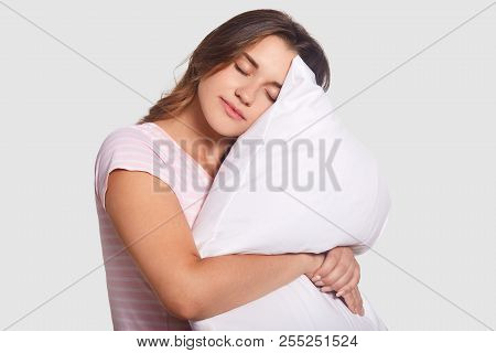People And Healthy Sleep Concept. Pretty Young Caucasian Woman Embraces White Soft Pillow, Closes Ey
