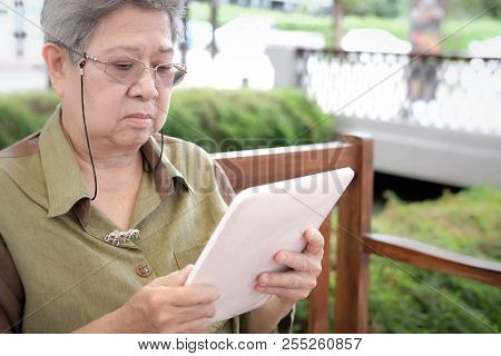 Elder Woman Holding Tablet. Elderly Senior Female Texting Message, Using App With Touchpad Outdoor