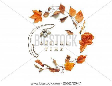 Autumn background - dry autumn leaves, old bronze clock in form of the owl and Autumn time letters on the white background. Autumn still life. Autumn composition