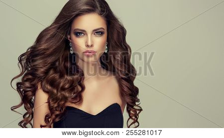 Brunette  Woman  With Long , Healthy And   Shiny Curly Hair .  Beautiful  Model Girl  With Wavy Hair