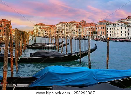 Venice, Italy, Jun 7, 2018: Moored Gondolas On Grand Canal With Colorful Buildings In The Background