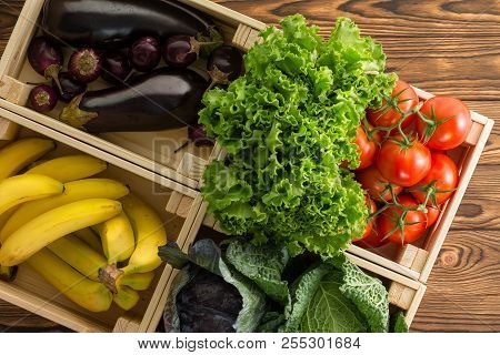 Assorted Fresh Organic Vegetables In Wooden Boxes On Display At A Farmers Market Viewed Close Up Fro