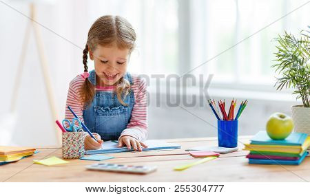 A Child  Girl  Doing Homework Writing And Reading At Home