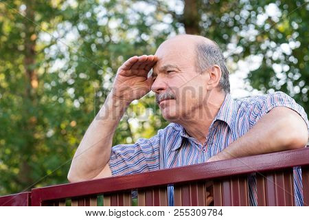 Mature Caucasian Man Carefully Watching Over The Fence.