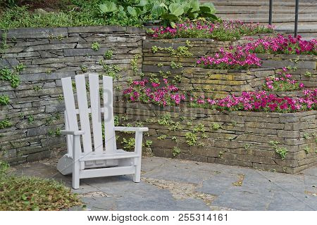 White Wooden Chair For Relaxing At Stone Wall With Flowers In Bloom