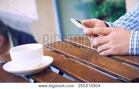 Man Using A Cell Phone On Cafe Terrace And Drinking Coffee. Man Drinks Coffee. Man Using Cellphone.
