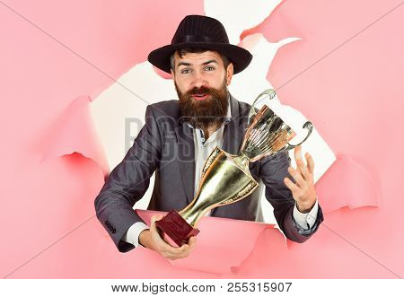Bearded Man Looking Through Hole Paper Holds Golden Trophy. Happy Business Man Holds Prize Cup. Busi