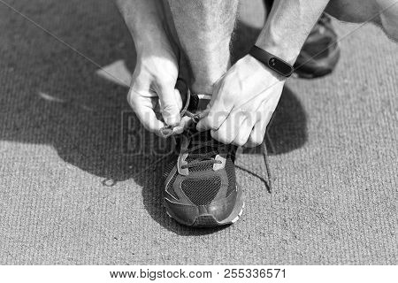 Hands Tying Shoelaces On Sneaker, Running Surface Background. Hands Of Sportsman With Pedometer Tyin