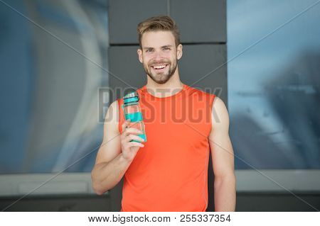 Sporty accessory. Man athlete hold special sporty bottle care hydration body after workout. Refreshing vitamin drink. Athlete drink water after training. Man athletic appearance holds water bottle. poster