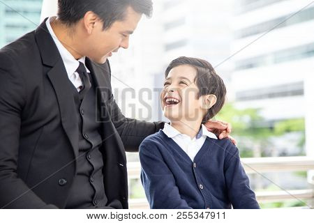 Portrait Of Boy Looking To Father With Attractive Smile. Business Man Talking With His Son With Happ