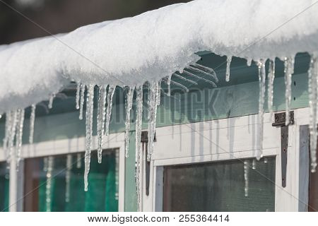 Icicles And Snow Hanging From A Gutter In Freezing Winter Conditions In England During The Beast Fro